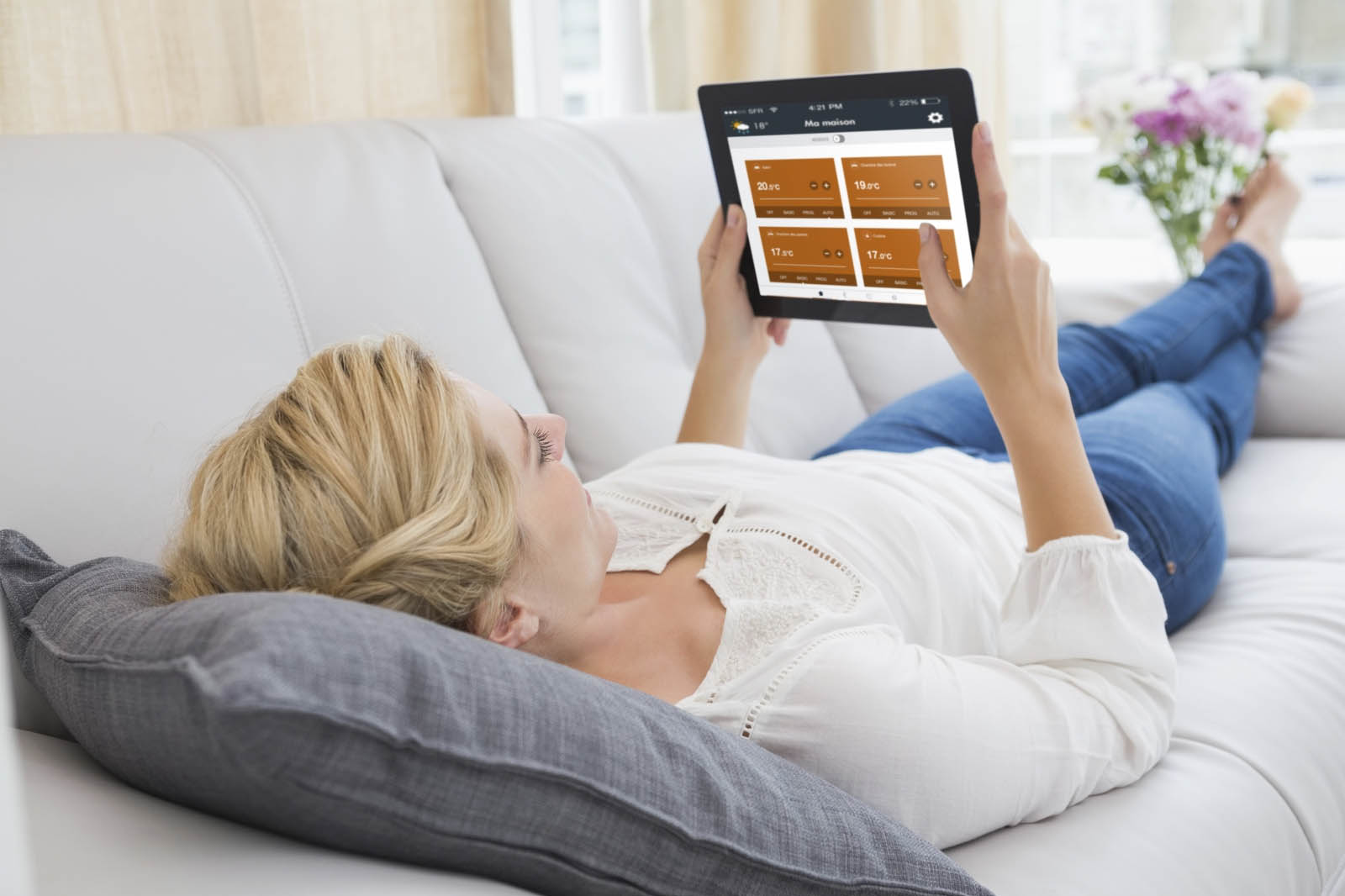 A woman relaxing with an electric heating smart controller app on a tablet
