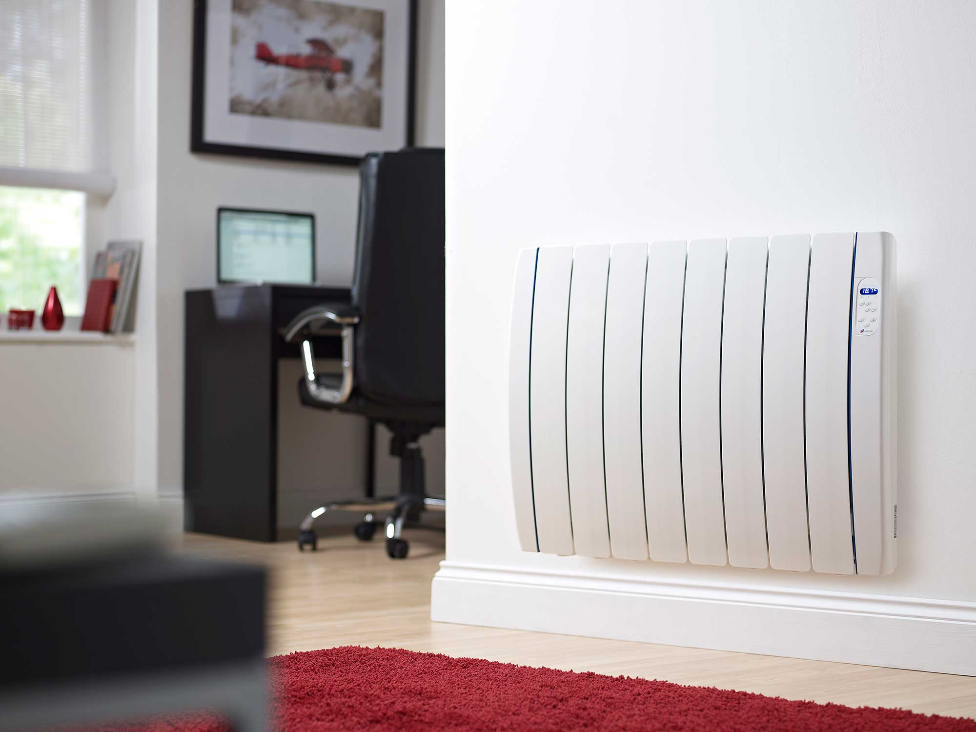 An electric radiator mounted to the wall with a home office in view