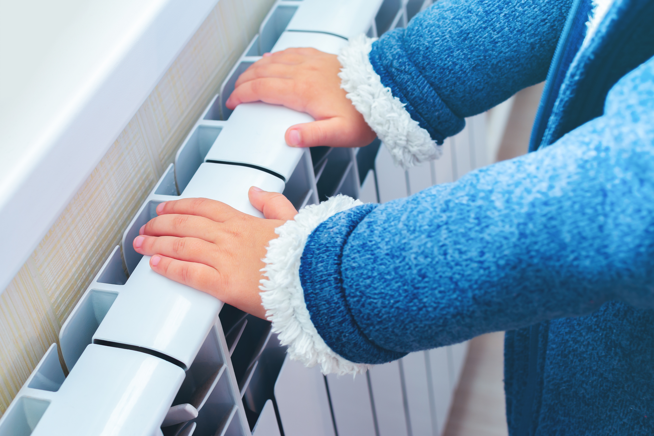 Child warming up their hands over an electric radiator at home