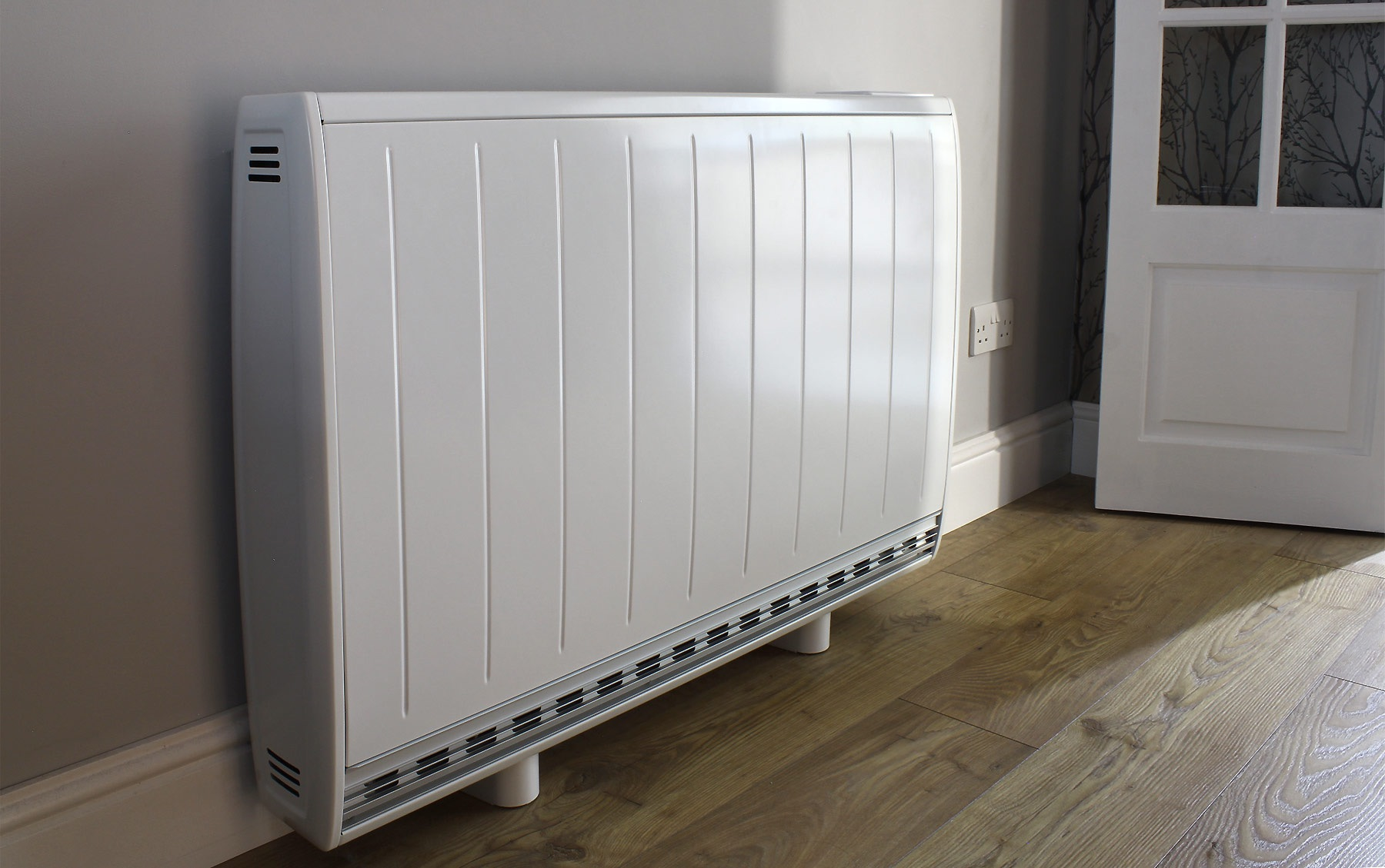 The Dimplex Quantum storage heater affixed to a wall in a modern looking corridor